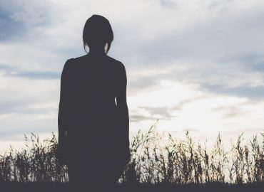 Silhouette of woman standing alone in a field at sunrise